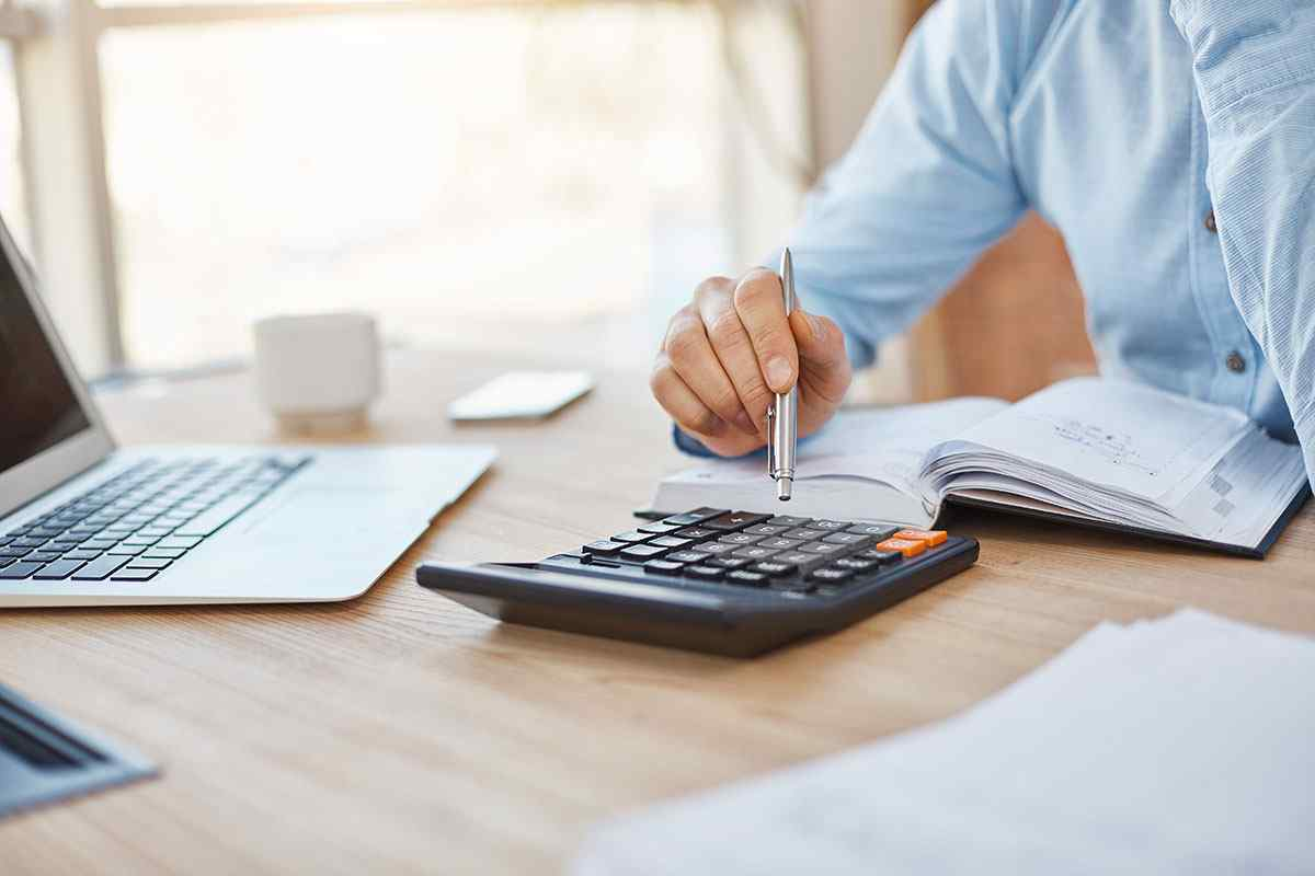 close-up-detail-professional-serious-accountant-sitting-light-office-checking-company-finance-profits-calculator (1)