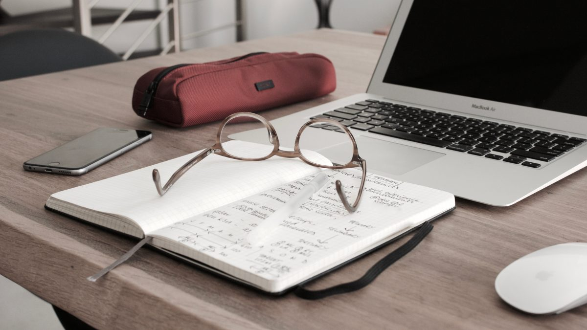 eyeglass with pen, notebook and laptop